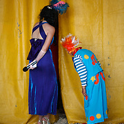The Mistress of Ceremonies and a clown watch inside the tent from behind curtains at the Cole Brother Circus in Wilmington, North Carolina.