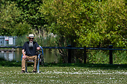 An old man brings his own chair to sit amongst a sea of daisies and from time to time get some exercise by walking to one edge and back - Clapham Common has begun to return to some form of normality as the effects of the Government easing of restrictions and sunny weather combine to encourage people out - Lambeth Council have now removed the signs and tape that stopped people sitting on benches. The eased 'lockdown' continues for the Coronavirus (Covid 19) outbreak in London.