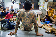 "14 MARCH 2014 - NAKHON CHAI SI, NAKHON PATHOM, THAILAND: A man relaxes between sessions to refresh his sak yant tattoo at Wat Bang Phra. Wat Bang Phra is the best known ""Sak Yant"" tattoo temple in Thailand. It's located in Nakhon Pathom province, about 40 miles from Bangkok. The tattoos are given with hollow stainless steel needles and are thought to possess magical powers of protection. The tattoos, which are given by Buddhist monks, are popular with soldiers, policeman and gangsters, people who generally live in harm's way. The tattoo must be activated to remain powerful and the annual Wai Khru Ceremony (tattoo festival) at the temple draws thousands of devotees who come to the temple to activate or renew the tattoos. People go into trance like states and then assume the personality of their tattoo, so people with tiger tattoos assume the personality of a tiger, people with monkey tattoos take on the personality of a monkey and so on. In recent years the tattoo festival has become popular with tourists who make the trip to Nakorn Pathom province to see a side of ""exotic"" Thailand.   PHOTO BY JACK KURTZ"