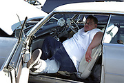 Fat man chilling in his car, complete with fluffy dice, Las Vegas, USA, 2000's