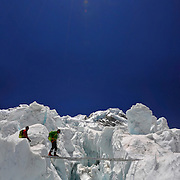 Panorama of Charley Mace crossing a ladder over a massive crevasse in the Khumbu Icefall on Mount Everest, Nepal.