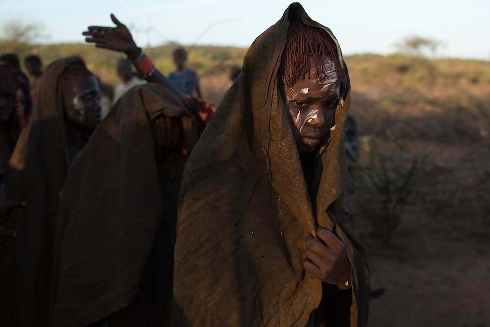 Pokot girls, covered in animal skins walk in line during  a circumcision tribal ritual.