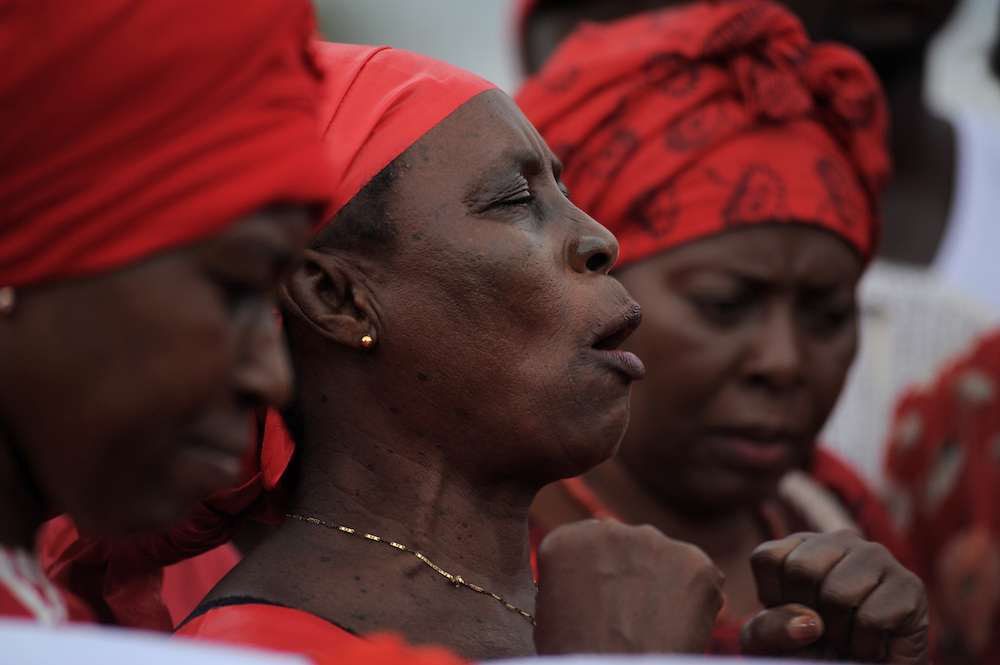 LOME, TOGO - 12-09-20   - A woman leads a prayer at the beginning of the protest. Approximately 300 women dressed in red marched through the Togolese capital city of Lomé on Thursday, September 20 as part of a protest organized by the opposition coalitions Lets Save Togo (Collectif Sauvons le Togo, CST) and Coalition ARC-EN-CIEL.  Several thousand men and youths joined the women in the peaceful march, which ended at an opposition rally point.  Photo by Daniel Hayduk/ AFP