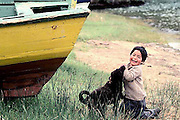 Boy and dog playing in boat yard