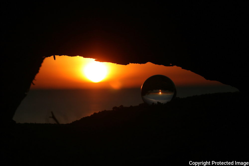 Crystal ball under log at sunset
