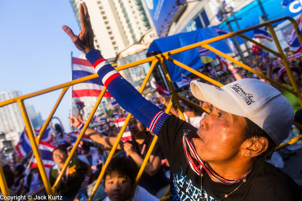 "13 JANUARY 2014 - BANGKOK, THAILAND: A Thai man waves to a TV news helicopter during an anti-government protest in Bangkok. Tens of thousands of Thai anti-government protestors took to the streets of Bangkok Monday to shut down the Thai capitol. The protest was called ""Shutdown Bangkok"" and is expected to last at least a week. The Shutdown Bangkok protest is a continuation of protests that started in early November. There have been shootings almost every night at different protests sites around Bangkok, including two Sunday night, but the protests Monday were peaceful. The malls in Bangkok stayed open Monday but many other businesses closed for the day and mass transit was swamped with both protestors and people who had to use mass transit because the roads were blocked.    PHOTO BY JACK KURTZ"