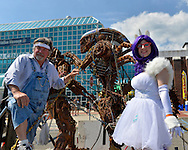 Garden City, New York, USA. 14th June 2015. HALE STORM of Freeport, the sculpture, and LAURA GIUNTA, of Levittown, cosplaying as Rarity from My Little Pony, pose, each holding a chain of The Predator and The Alien sculpture by artist Storm, outdoors at Eternal Con, the Long Island Comic Con, at the Cradle of Aviation museum. The sculptor created the life-size metal artwork from automotive and motorcycle parts.