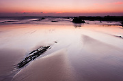 A thin film of water is left over the sand providing some reflections for the sunset sky at Amoreira Beach at one of the most scenic natural parks in Portugal, the Alentejo Southwest and Vicentina Coast.