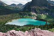 "See powder blue Grinnell Lake on the Grinnell Glacier Trail in Glacier National Park, Montana, USA. Since 1932, Canada and USA have shared Waterton-Glacier International Peace Park, which UNESCO declared a World Heritage Site (1995) containing two Biosphere Reserves (1976). Rocks in the park are primarily sedimentary layers deposited in shallow seas over 1.6 billion to 800 million years ago. During the tectonic formation of the Rocky Mountains 170 million years ago, the Lewis Overthrust displaced these old rocks over newer Cretaceous age rocks. Glaciers carved spectacular U-shaped valleys and pyramidal peaks as recently as the Last Glacial Maximum (the last ""Ice Age"" 25,000 to 13,000 years ago). Of the 150 glaciers existing in the mid 1800s, only 25 active glaciers remain in the park as of 2010, and all may disappear as soon as 2020, say climate scientists."