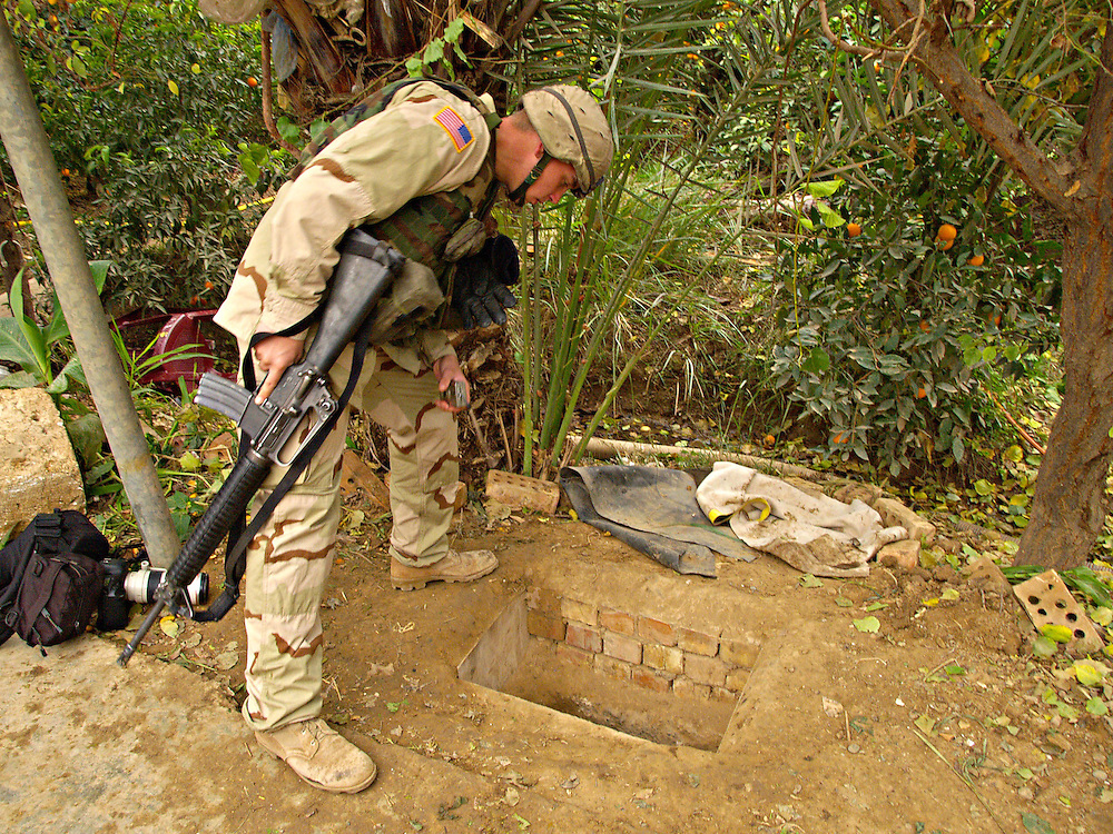 Dec15th 2003.ad Dawr, Iraq..Saddams hideout..A US soldier peers into the hole in which Saddan was discovered in the yard of a small farmhouse near Tikrit...15th December 2003