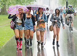© London News Pictures. 07/07/2012. Rain soaked revellers hide underneath umbrellas on their way to Wireless Festival in Hyde Park, London on July 7, 2012. The environment agency has issued severe weather warnings with three inches of rain falling in 24 hours in some parts.  Photo credit: Ben Cawthra/LNP.