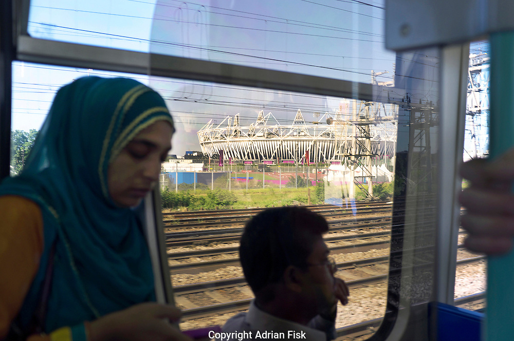 Passangers on the DLR (Docklands light railway) pass by the Olympic stadium in Stratford in East London