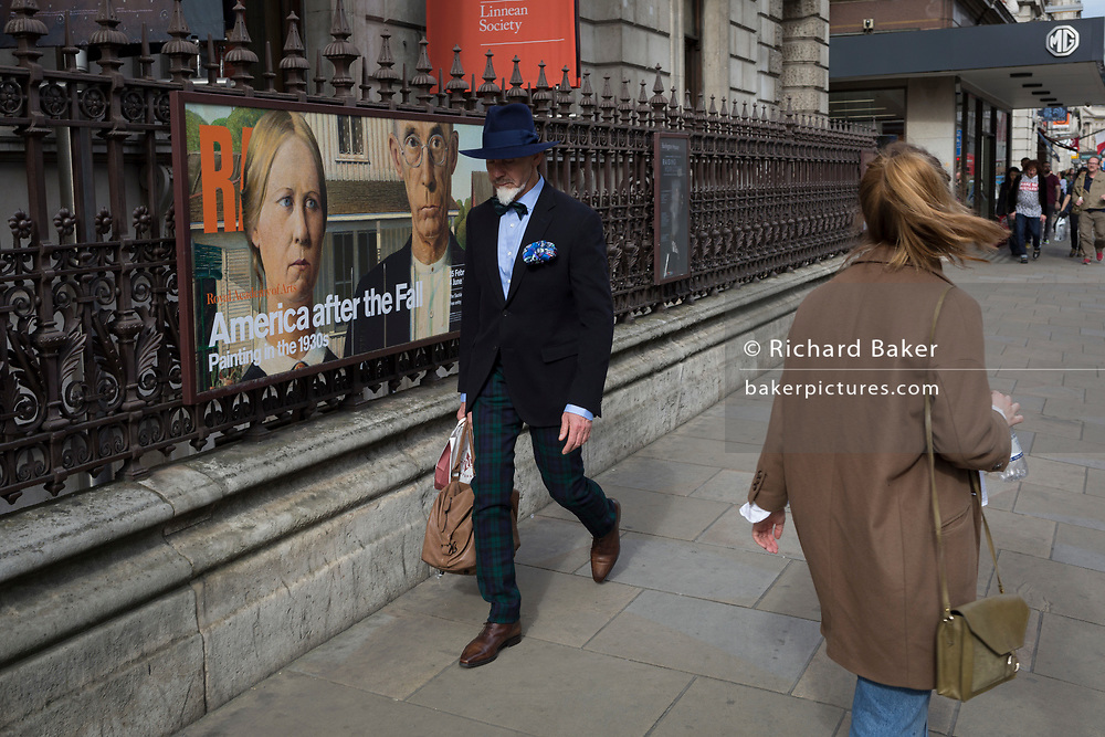 Dapper gentleman walks past American Gothic poster, outside the Royal Academy on Piccadilly, on 30th March 2017, in London, England.