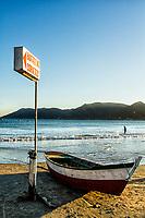 Barco sobre a areia e pescador ao fundo na Praia do Pântano do Sul. Florianópolis, Santa Catarina, Brasil. / Boat on the sand and fisherman in the background at Pantano do Sul Beach. Florianopolis, Santa Catarina, Brazil.