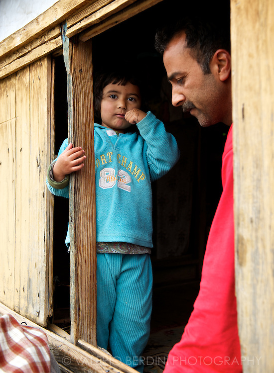 A father and his son inside their houseboat. Dal Lake Srinagar. Kashmir. India