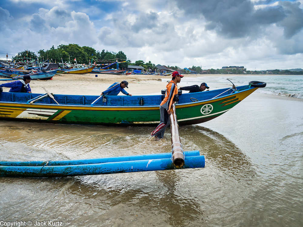 18 JULY 2016 - KUTA, BALI, INDONESIA:  A fishing crew pushes their outrigger canoe into the ocean to go fishing from Pasar Ikan pantai Kedonganan, a fishing pier and market in Kuta, Bali.   PHOTO BY JACK KURTZ