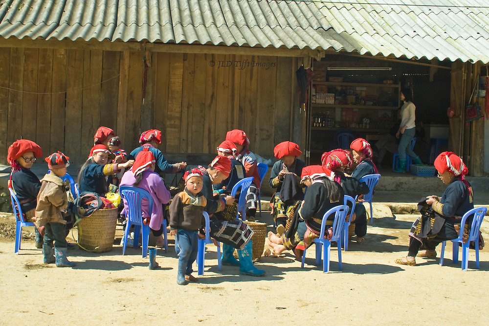 Ten adult Red H'mong women seated in a group talk and sew in a community activity.  Several toddlers stand among them, clearly being babysat by their working mothers.