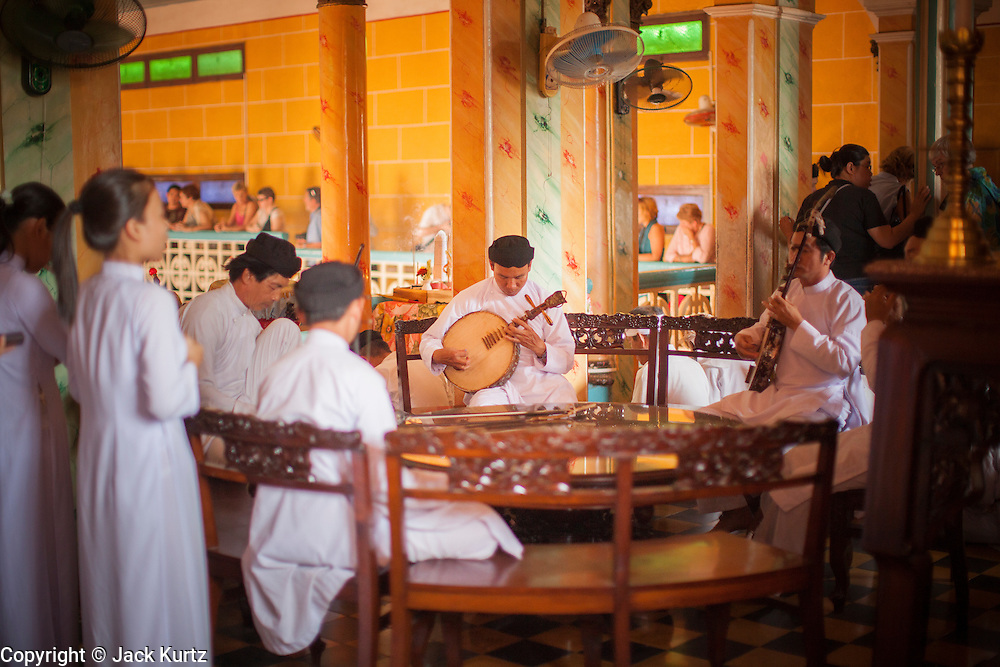 """29 MARCH 2012 - TAY NINH, VIETNAM:  A musician leads performs during noon prayers at the Cao Dai Holy See in Tay Ninh, Vietnam. Cao Dai (also Caodaiism) is a syncretistic, monotheistic religion, officially established in the city of Tây Ninh, southern Vietnam in 1926. Cao means """"high"""" and """"Dai"""" means """"dais"""" (as in a platform or altar raised above the surrounding level to give prominence to the person on it). Estimates of Cao Dai adherents in Vietnam vary, but most sources give two to three million, but there may be up to six million. An additional 30,000 Vietnamese exiles, in the United States, Europe, and Australia are Cao Dai followers. During the Vietnam's wars from 1945-1975, members of Cao Dai were active in political and military struggles, both against French colonial forces and Prime Minister Ngo Dinh Diem of South Vietnam. Their opposition to the communist forces until 1975 was a factor in their repression after the fall of Saigon in 1975, when the incoming communist government proscribed the practice of Cao Dai. In 1997, the Cao Dai was granted legal recognition. Cao Dai's pantheon of saints includes such diverse figures as the Buddha, Confucius, Jesus Christ, Muhammad, Pericles, Julius Caesar, Joan of Arc, Victor Hugo, and the Chinese revolutionary leader Sun Yat-sen. These are honored at Cao Dai temples, along with ancestors.      PHOTO BY JACK KURTZ"""