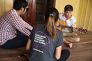 ICS volunteers Dan Hensman playing his guitar to his fellow volunteers and host home family members on the balcony of their host home, in the village of in Banteay Char, near Battambang, Cambodia.