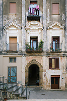 """PISCIOTTA, ITALY - 22 APRIL 2018: The facade of a building is seen here in the main square of the historical center of Pisciotta, Italy, on April 22nd 2018.<br /> <br /> Former restaurant owners Donatella Marino and her husband Vittorio Rimbaldo have spent the recent years preparing and selling salted anchovies, called alici di menaica, to a growing market thanks to a boost in visibility from the non-profit Slow Food.  The ancient Menaica technique is named after the nets they use brought by the Greeks wherever they settled in the Mediterranean. Their process epitomizes the concept of slow food, and involves a nightly excursion with the special, loose nets that are built to catch only the larger swimmers. The fresh, red anchovies are immediately cleaned and brined seaside, then placed in terracotta pots in between layers of salt, to rest for three months before they're aged to perfection.While modern law requires them to use PVC containers for preserving, the government recently granted them permission to use up to 10 chestnut wood barrels for salting in the traditional manner. The barrels are """"washed"""" in the sea for 2-3 days before they're packed with anchovies and sea salt and set aside to cure for 90 days. The alici are then sold in round terracotta containers, evoking the traditional vessels that families once used to preserve their personal supply.<br /> <br /> Unlike conventional nets with holes of about one centimeter, the menaica, with holes of about one and half centimeters, lets smaller anchovies easily swim through. The point may be to concentrate on bigger specimens, but the net also prevents overfishing."""