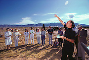 First atomic bomb test site: Site Trinity ground zero, the still radioactive piece of desert in the White Sands Missile Range was witness to the world's first nuclear explosion on August 6, 1945. Each year the site is open to the public for one day. An exorcism is performed by a Catholic Priest, here sprinkling holy water, as visitors to ground zero mill around an original Fat Man bomb casing, on loan from the nearby Atomic Museum in Albuquerque, New Mexico. 1986.