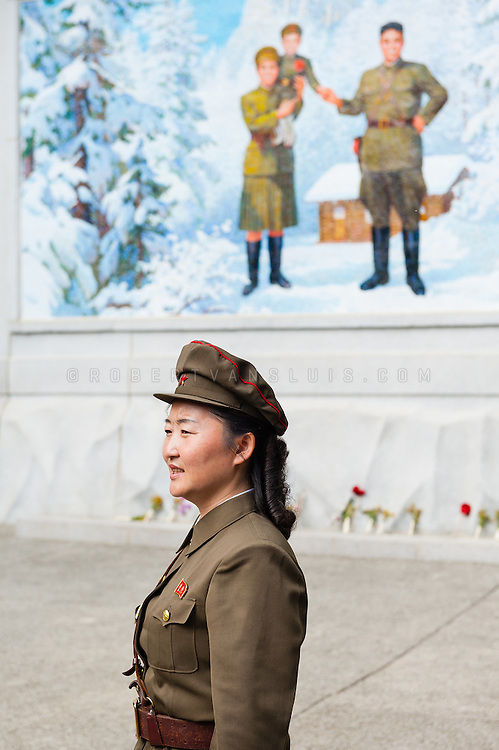 Guide in front of a mural of Kim Jong Il's family at Mount Paekdu Secret Camp, DPRK (North Korea)
