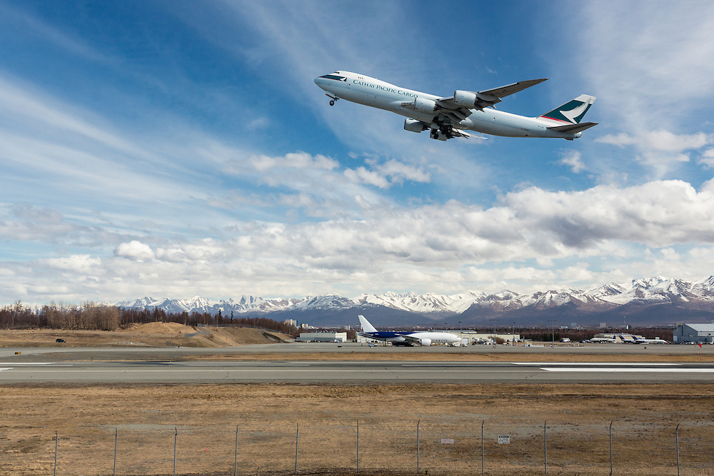 Cathay Pacific Cargo jet taking off from Ted Stevens Anchorage International Airport in Southcentral Alaska with the Chugach Mountains in the background. Spring. Afternoon.