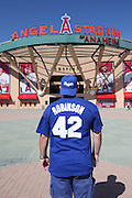 ANAHEIM, CA - APRIL 15:  A Los Angeles Dodgers fan wears a Jackie Robinson jersey as he looks at the exterior facade of Angel Stadium before the Los Angeles Angels of Anaheim game against the Oakland Athletics at Angel Stadium on Tuesday, April 15, 2014 in Anaheim, California. The Athletics won the game 10-9 in eleven innings. (Photo by Paul Spinelli/MLB Photos via Getty Images)