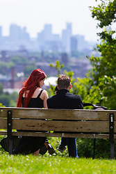 A couple on Parliament Hill in Noth London relax on a bench overlooking the skyscrapers of the City. London, May 26 2019.
