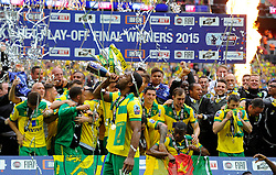 Norwich City's Cameron Jerome drinks from a champagne bottle in front of team mates with the trophy as Norwich City win promotion to the premier league   - Photo mandatory by-line: Joe Meredith/JMP - Mobile: 07966 386802 - 25/05/2015 - SPORT - Football - London - Wembley Stadium - Middlesbrough v Norwich - Sky Bet Championship - Play-Off Final