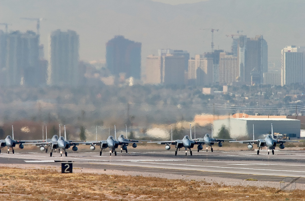 Two groups of four F-15C Eagles prepare to depart runway 3L with the ever growing Las Vegas skyline in the background. A typical mission during Red Flag can consist of more than 70 aircraft including fighters, bombers, aerial refuelers, electronic countermeasures, aggressors, airborne command and control and others. Though the majority of aircraft occupying the range are fighters, it takes all of these various support aircraft to insure a successful and realistic mission.