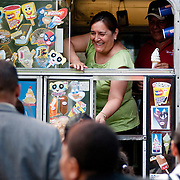August 3, 2010 - Bronx, NY : The 50th Precinct held its annual Night Out on Tuesday, August third in Mabrle Hill. The Five Oh chipped in with local vendors to supply treats and games for the community and ended with evening with a prize raffle. Else Polo, in green, smiles as she hands a child an ice cream cone.