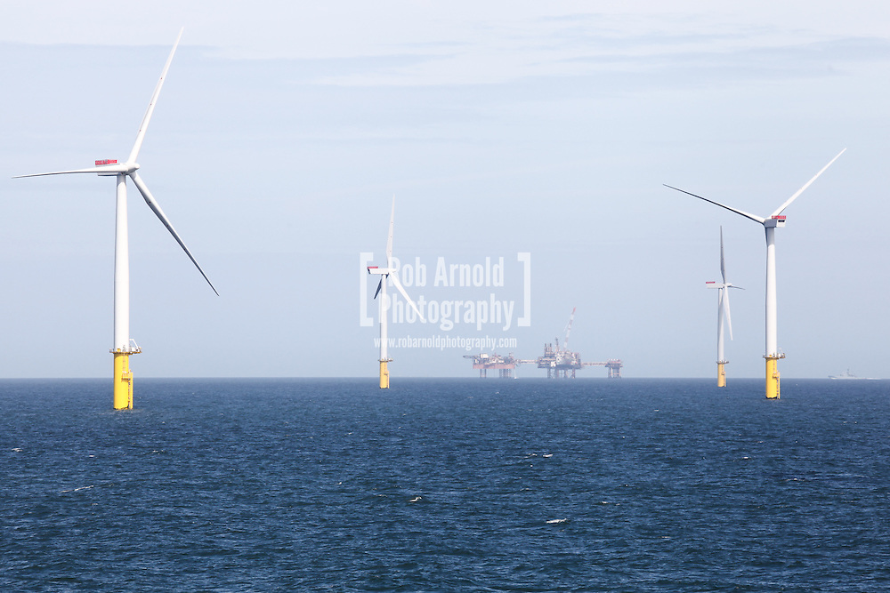 © Rob Arnold.  09/04/2014. North Wales, UK. Wind turbines of the Gwynt y Môr Offshore Wind Farm, with the oil platforms of the Douglas Complex, operated by BHP Billiton, visible in the distance. Photo credit : Rob Arnold
