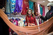Hind, Ramah and Souad shop for sari's in the Whitechapel area of London. With the purchased fabrics they go to their tailors and have colorful party dresses made. London, UK, 2012