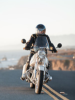 Brent Greenwood (MR) riding his 1960s BMW R60US motorcycle (PR) on a coastal road in Sonoma County California.
