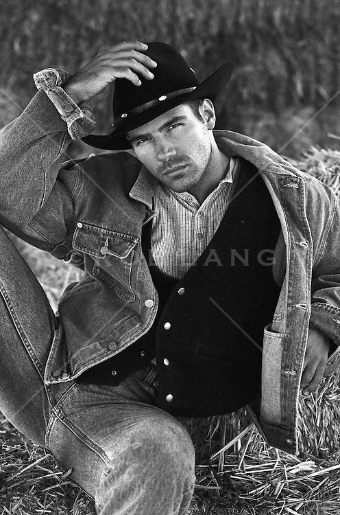 cowboy sitting in a hay barn