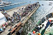 De Arctic Sunrise meert aan in Amsterdam. In IJmuiden is de Arctic Sunrise, het schip van milieuorganisatie Greenpeace dat een jaar door Rusland in beslag is genomen, aangekomen. De voormalige ijsbreker wordt in Amsterdam uit het water gehaald en opgeknapt omdat het gehavend is geraakt toen het aan de ankers lag. De boot van de milieuorganisatie is september 2013 door de Russen ge&euml;nterd en de bemanningsleden vastgezet op verdenking van piraterij. Greenpeace voerde actie bij een boorplatform in de Barentszzee. Als het schip weer is gerepareerd, wil de milieubeweging weer campagnes houden met de Artic Sunrise.<br /> <br /> In IJmuiden, the Arctic Sunrise, the Greenpeace ship that a year ago is seized by Russia, arrived. The former ice breaker is removed from the water in Amsterdam and refurbished since it was damaged when it was up to the anchors. The boat of the environmental organization is boarded in September 2013 by the Russians and the crew put down on suspicion of piracy. Greenpeace campaigned on a drilling platform in the Barents Sea. If the ship is repaired, the environmental movement wants to use the Arctic Sunrise again for campaigning.