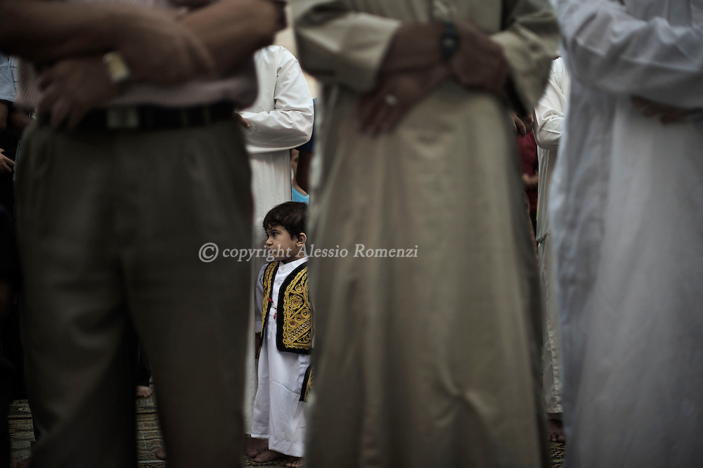 Gaza Strip, Gaza City: A Palestinian child stands in the al-Omari mosque courtyard as adults perform the prayer on Eid Al Fitr holiday on July 28, 2014. ALESSIO ROMENZI