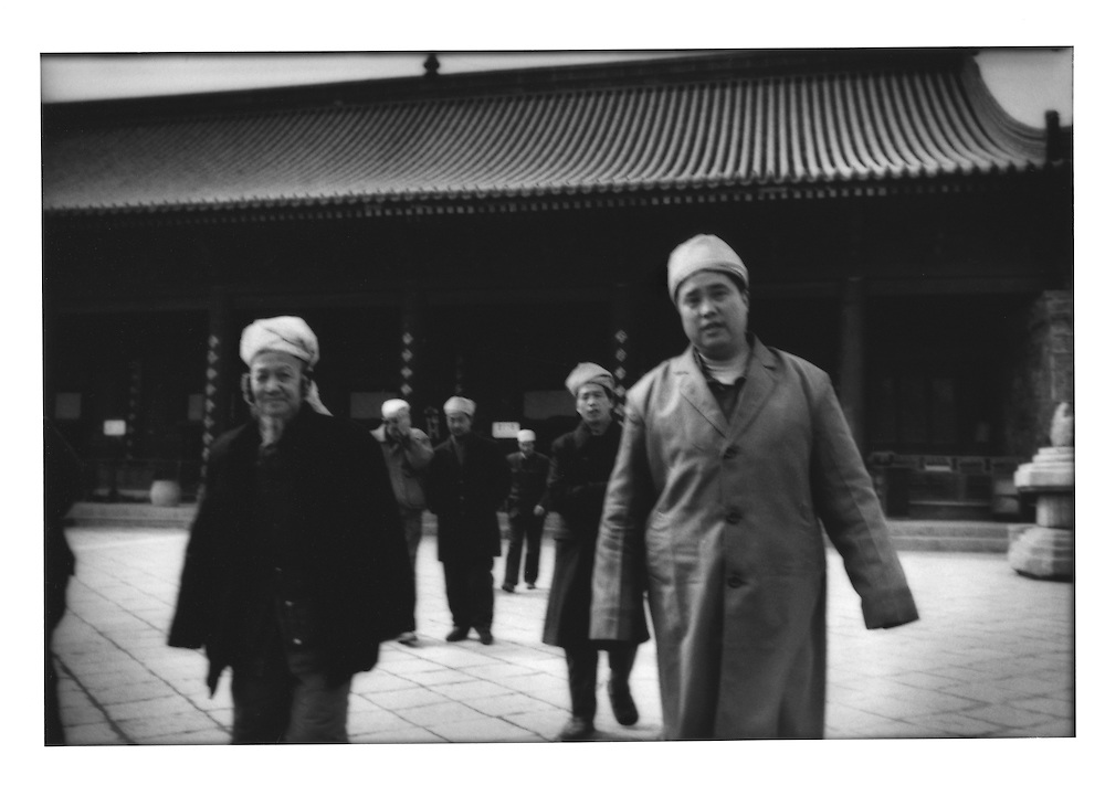 Hui Muslim elders file out of the Great Mosque (Daqingzhen Si) of Xian built in Chinese temple style in the 18th century, Xian, China.  Xian was both China's ancient capital and the terminus of the Silk Road.