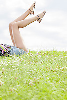 Low section of young woman with feet up lying on grass against sky