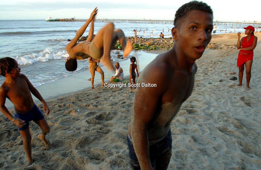 Boys practice flips on the beach in Riohacha, on Colombia's Caribbean coast, on Sunday, December 11, 2005. (Photo/Scott Dalton)