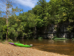 Kayakers rest at a tranquil beach on the upper Current River at the backcountry Cedargrove Campground located within the Ozark National Scenic Riverways. The Current River is the most spring-fed of all the rivers in the Missouri Ozarks. The river is a favorite with paddlers who enjoy the cold crystal clear water from springs that feed the Current River, including Cave Spring, Pulltite Spring, Round Spring, Blue Spring, and Big Spring. The scenic river is lined with rock ledges, caves, gravel bars and bluffs.<br /> <br /> The Ozark National Scenic Riverways was established in 1964, making it America's first national park area to protect a wild river system. The Ozark National Scenic Riverways, which include the Current and Jacks Fork rivers, is known for its caves, springs, sinkholes and losing streams. Visitors can enjoy water activities, such as floating, canoeing, tubing, swimming, and fishing. Additionally, there are opportunities for hiking, horseback riding, and wildlife viewing. Over 130 miles of waterways and 300 identified caves exist within the park.