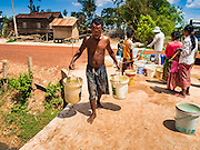 03 JUNE 2016 - SIEM REAP, CAMBODIA: A man carries water to his home after his jugs were filled at a water distribution point in Sot Nikum, a village northeast of Siem Reap. Wells in the village have been dry for more than three months because of the drought that is gripping most of Southeast Asia. People in the community rely on water they have to buy from water sellers or water brought in by NGOs. They were waiting for water brought in by truck from Siem Reap by Water on Wheels, a NGO in Siem Reap. Cambodia is in the second year of  a record shattering drought, brought on by climate change and the El Niño weather pattern. There is no water to irrigate the farm fields and many of the wells in the area have run dry.     PHOTO BY JACK KURTZ