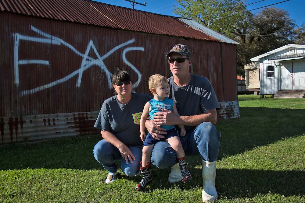 Gros family in their yard on La 977.  Mike Gros painted an anti-FAS sign on a storage shack in his yard after yard signs he and his neighbors put up were stolen.