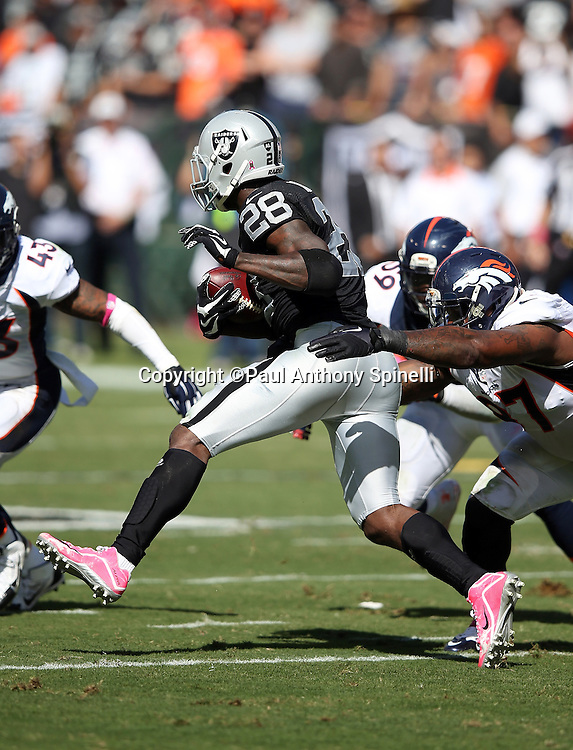 Oakland Raiders running back Latavius Murray (28) tries to elude a tackle attempt by Denver Broncos defensive end Malik Jackson (97) as he runs the ball during the 2015 NFL week 5 regular season football game against the Denver Broncos on Sunday, Oct. 11, 2015 in Oakland, Calif. The Broncos won the game 16-10. (©Paul Anthony Spinelli)
