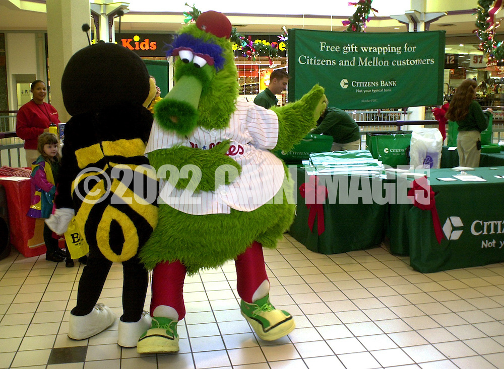 """The Phillie Phanatic, right, and the """"B101 Bee"""", a local radio station mascot, dance at the Citizens Bank gift wrapping stand, at the Granite Run Mall, Friday, Dec. 14, 2001, in Media, Pa. Citizens Bank is celebrating it's arrival in Pennsylvania , and thanking it's customers with free gift wrapping service at five Pennsylvania malls. (Photo by William Thomas Cain/photodx.com)"""