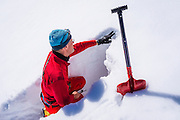 Backcountry skier checking snow conditions in a trench, Grand Teton National Park, Wyoming USA