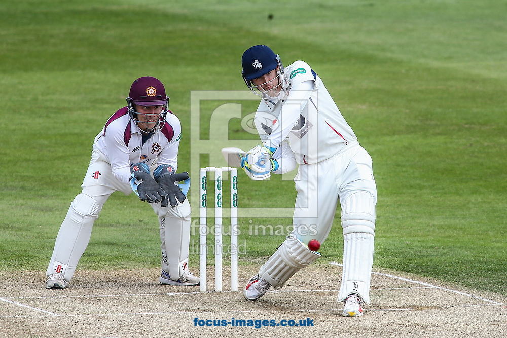 Joe Denly of Kent (right) hits out as Adam Rossington of Northamptonshire CCC (left) looks on during the Specsavers County C'ship Div Two match at the County Ground, Northampton<br /> Picture by Andy Kearns/Focus Images Ltd 0781 864 4264<br /> 16/05/2016
