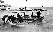 "The James Caird lifeboat is launched from the shore of Elephant Island in the South Shetland Islands on 24 April 1916. This photograph, probably captured by expedition photographer Frank Hurley, was published in the United States in Ernest Shackleton's 1919 book, ""South,"" from William Heinemann publishing house of London. The voyage of the James Caird, one of history's greatest small-boat journeys, was by open whaleboat from Elephant Island to South Georgia in the southern Atlantic Ocean, a distance of 800 nautical miles (1500 km; 920 mi) across one of the world' s most treacherous seas. Undertaken by expedition leader Sir Ernest Shackleton and five companions, its objective was to obtain rescue for the main body of the Imperial Trans-Antarctic Expedition of 1914-17, trapped on Elephant Island after the loss of their ship Endurance. On the temporary haven of Elephant Island, the expedition's carpenter, Harry McNish, improvised tools and materials to adapt the 22.5-foot (6.9 m) long James Caird, raising its sides and building a makeshift deck of wood and canvas, sealing the work with oil paints, lamp wick, and seal blood. The craft was further strengthened with a mast lashed inside along the length of her keel, and fitted with a mainmast and a mizzenmast, rigged to carry lugsails and a jib. Boat weight was increased by 1 long ton (1016 kg) of ballast, to lessen the risk of capsizing in the high seas that Shackleton knew would be encountered. (This photo is in the public domain in the United States because its first publication occurred prior to January 1, 1923.)"
