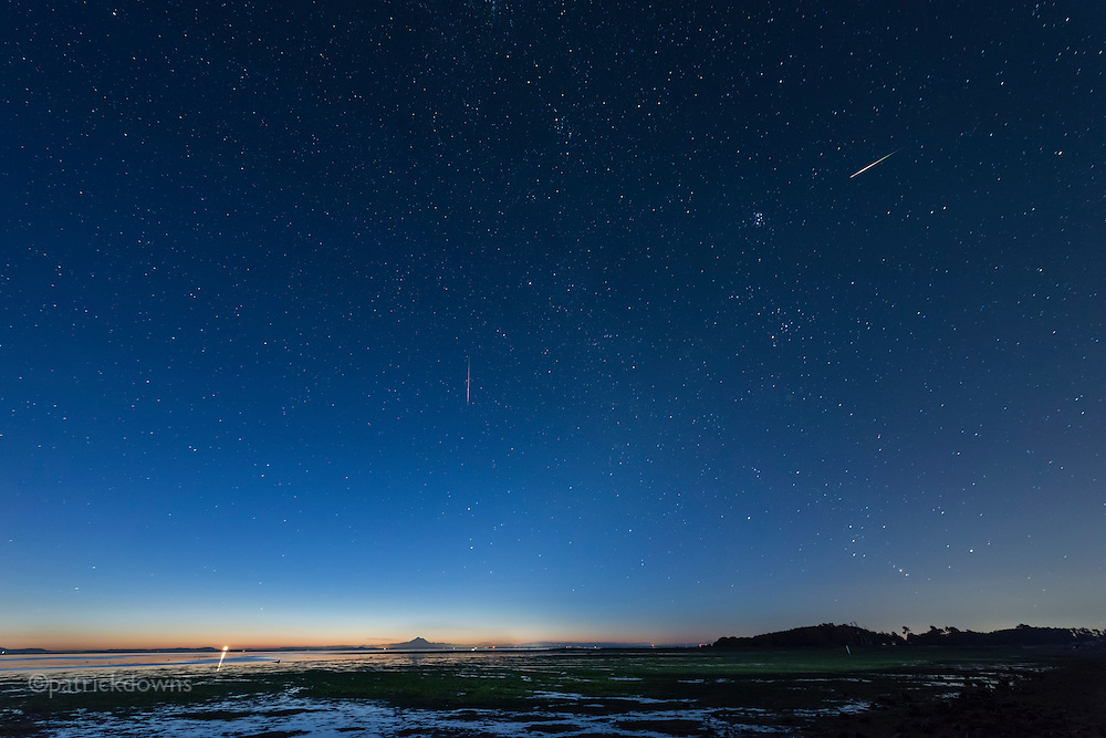 Perseid meteors fly above the Strait of Juan de Fuca (the Salish Sea), as Mt. Baker emerges from the pre-dawn over 60 miles away. The bright light is the Dungeness Spit lighthouse in the Strait, at the end of the the 5 mile long Dungeness Spit. (4:12am, August 12, 2016)